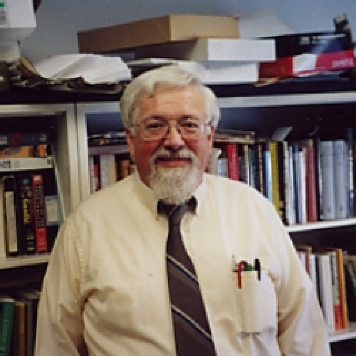 Dr. John O'Connor standing in front of bookcase.