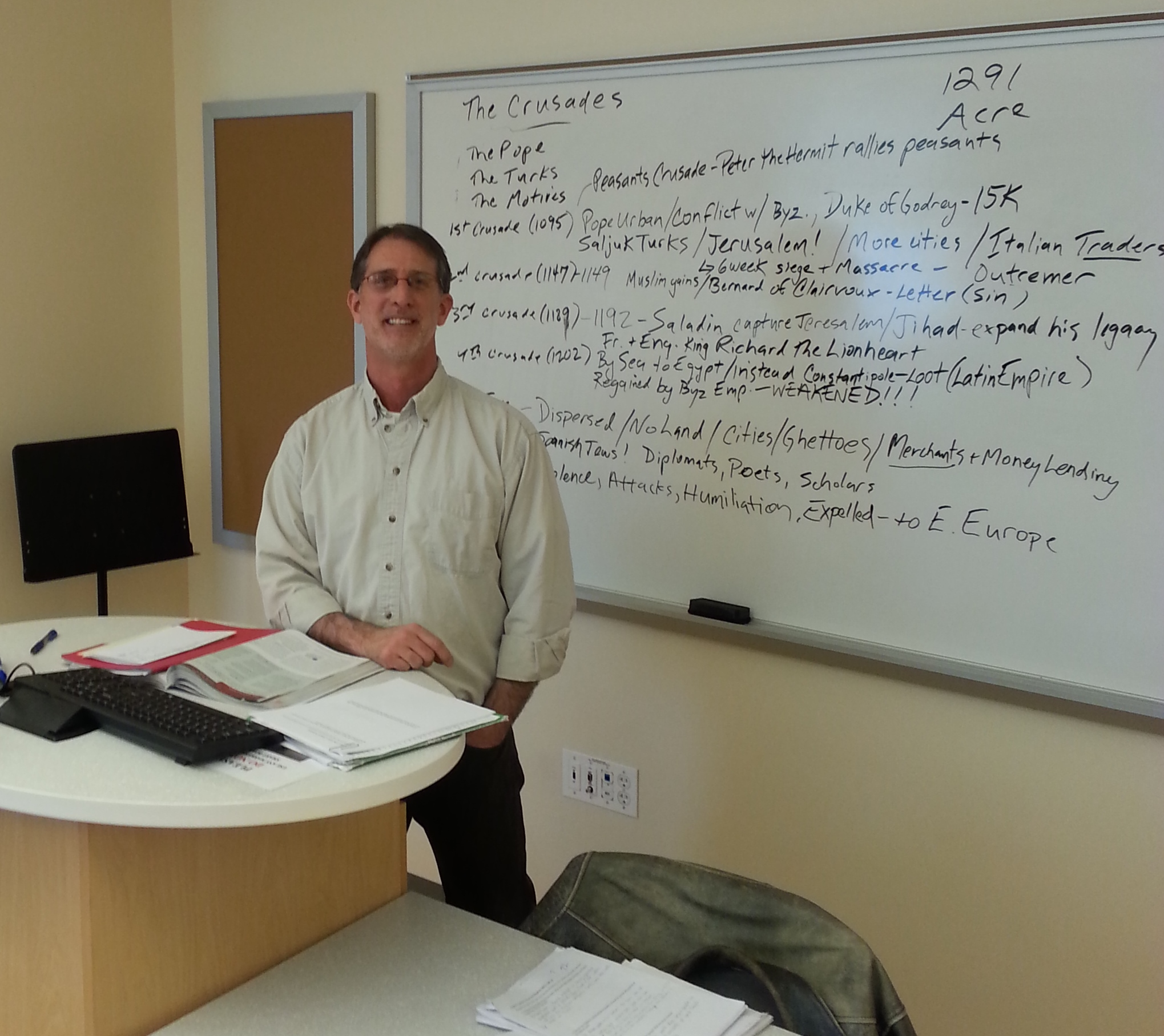 Gene Smith standing in front of a white board with notes on the crusades.