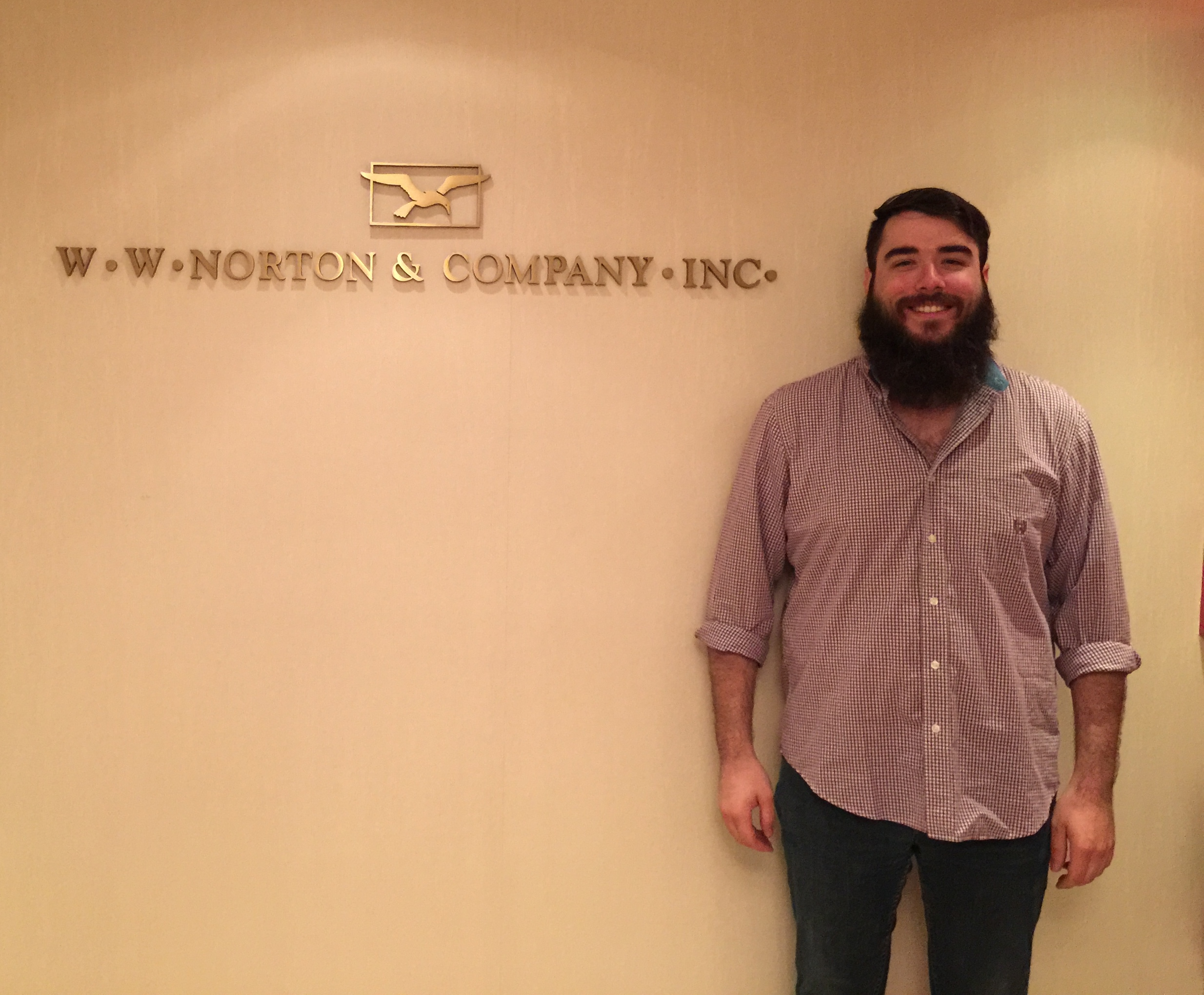 "Chris Hillyer stands in front of golden lettering on a wall reading ""W.W. Norton Company, Inc."" with logo of box and flying gull."