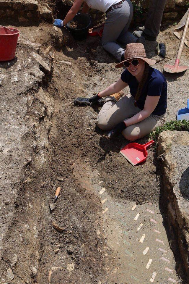 MacGregor looks up from trench revealing uncovered mosaic tile