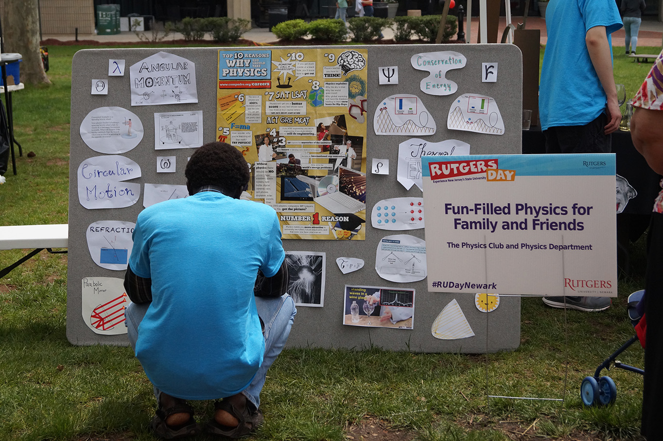 A visitor looks at a board explaining physics concepts.