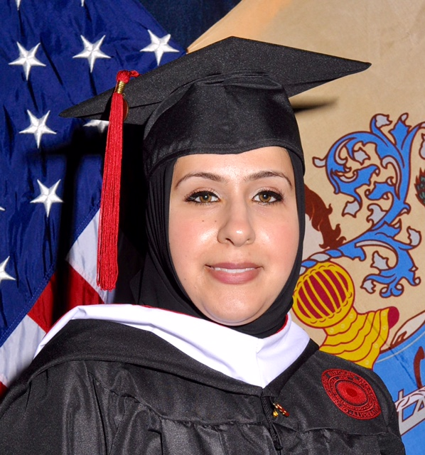 Shereen Ramadan in graduation cap standing in front of American flag and a blue crest.
