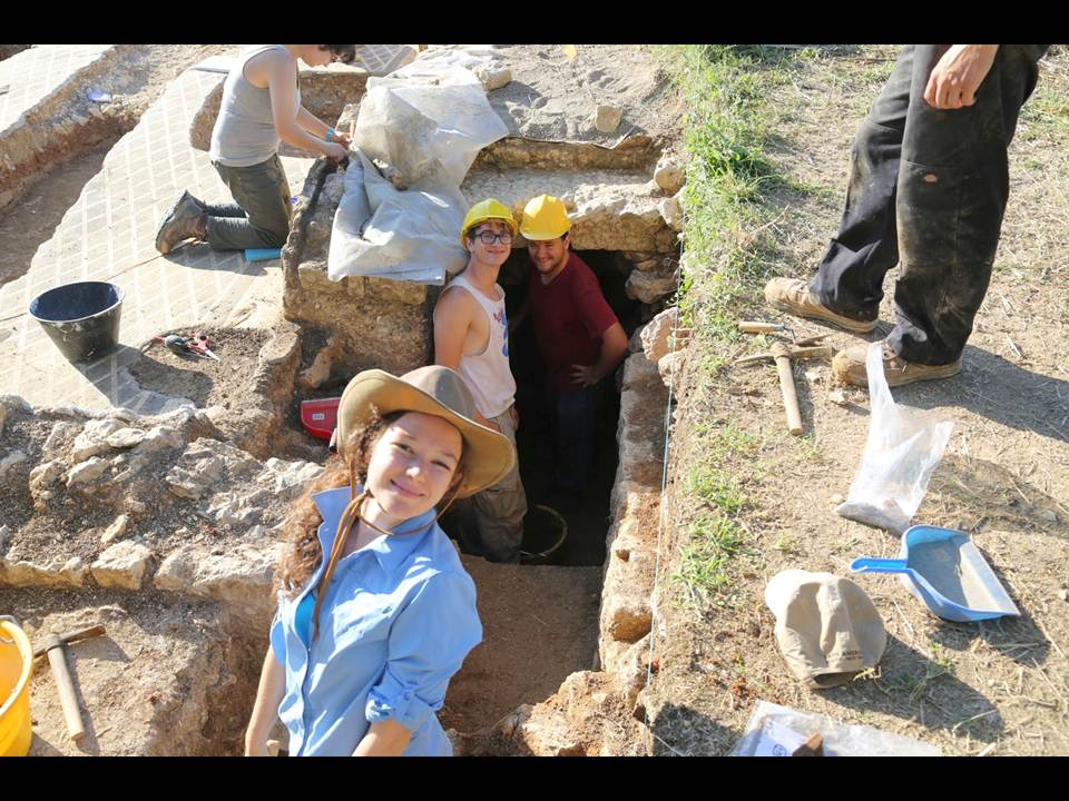 Students peering up from excavation site and dust off earth from the ruins.