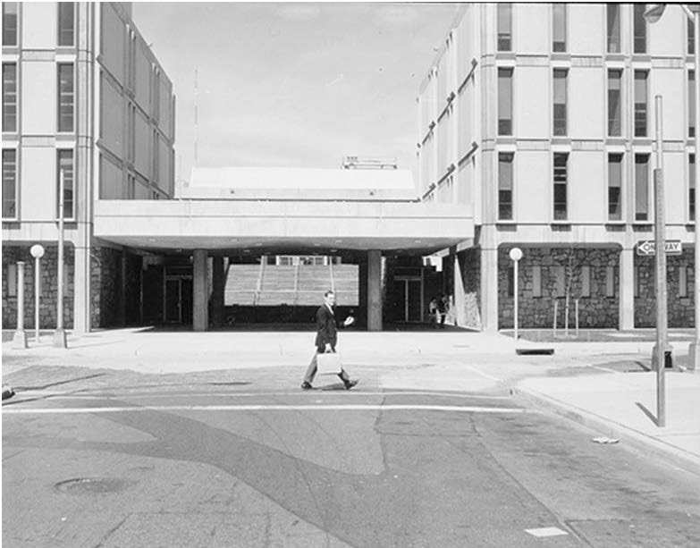 image from Dana Library photo collection of man in suit walking in front of building