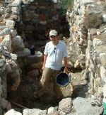 Notarian standing in stone trench at site holding bucket