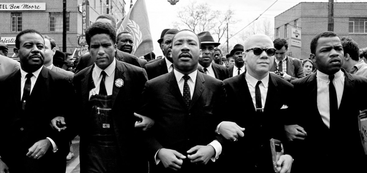 "From left, Ralph Abernathy, James Forman, the Rev. Dr. Martin Luther King Jr., the Rev. Jesse Douglas and John Lewis lead a march from Selma to Montgomery in 1965, in a scene from the Paramount documentary ""I Am MLK Jr."""