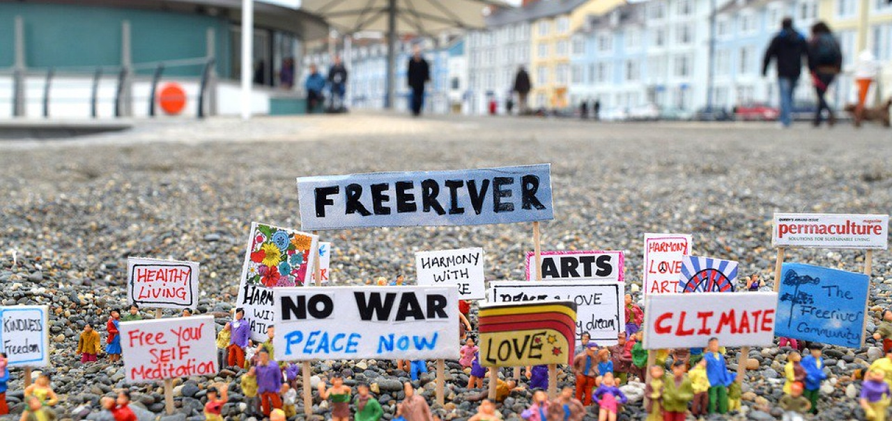 Signs with anti-war and environmental slogans on gravel