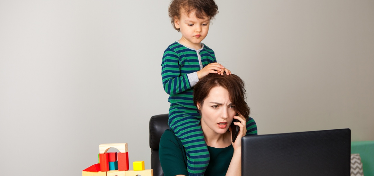 Mom at laptop, on the phone, with a toddler on her shoulders
