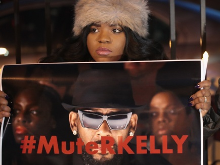 Woman holding #MuteRKelly sign