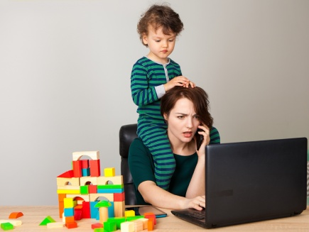 mom at laptop, on the phone, with toddler on her shoulders