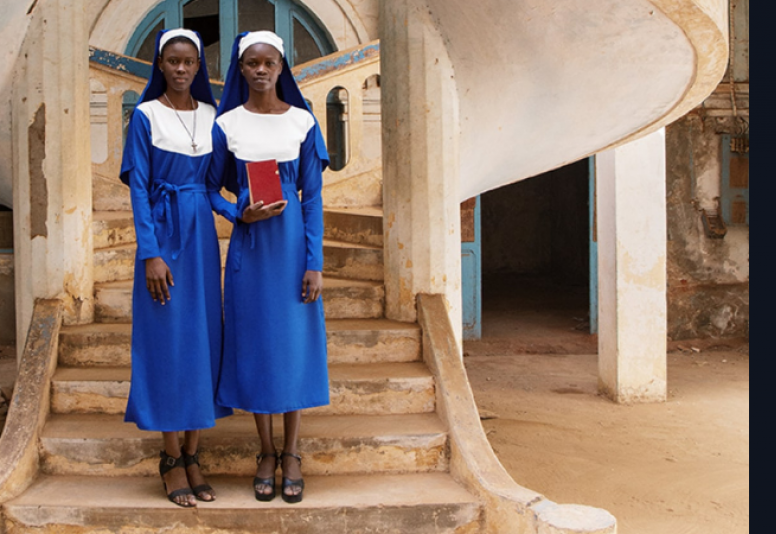 Two nuns in blue habits standing at the bottom of the staircase of a tawny-colored building in the background.  The nun on the left's arm is tucked behind the other who holds a small rust colored book.